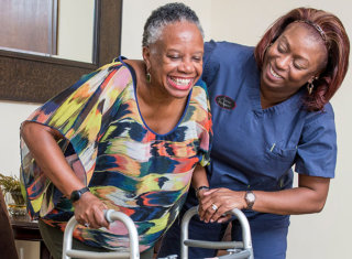 caregiver assisting the elder woman with walkers