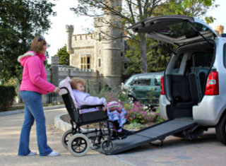 caregiver transporting an elderly woman in a wheelchair