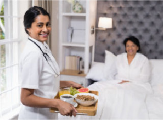 Caregiver serving meal for an elderly woman