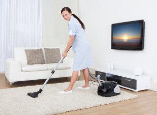 caregiver vacuuming the carpet